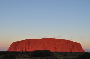 Vista of Uluru at sunset, reflecting red and gold