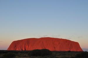 Vista of Uluru at sunset, reflecting red and gold