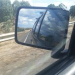 view of the road in the side mirror of the van