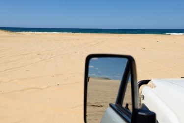 View of the beach from the car, with the sand dunes and blue sky in the side mirror