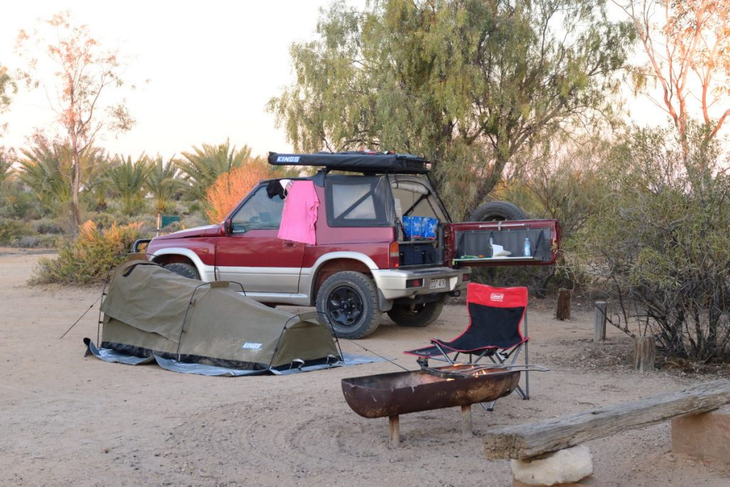 My campsite, Suzuki Vitara, swag and fire pit, surrounded by trees